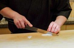 O cozinheiro chefe mestre prepara o corte do calamar fresco para o sashimi imagem de stock royalty free