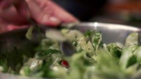 O cozinheiro chefe mistura ingredientes da salada vegetal em uma bacia Salada da preparação video estoque