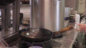 O cozinheiro chefe mistura ingredientes no ar em um frigideira chinesa no fogo no rastorane da cozinha filme