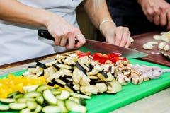O cozinheiro chefe na cozinha prepara o alimento saudável com vegetais fotos de stock royalty free