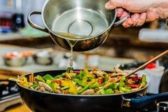 O cozinheiro chefe na cozinha prepara o alimento saudável com vegetais foto de stock royalty free