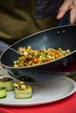 O cozinheiro chefe na cozinha prepara o alimento saudável com vegetais foto de stock