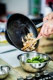 O cozinheiro chefe na cozinha prepara o alimento saudável com vegetais imagens de stock