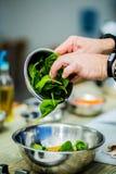 O cozinheiro chefe na cozinha prepara o alimento saudável com vegetais fotografia de stock