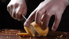 O cozinheiro chefe nas luvas corta o queijo com uma faca Restaurante Serviço da tabela vídeos de arquivo