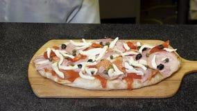 O cozinheiro chefe nas luvas de cozimento pretas que fazem a pizza que encontra-se em uma placa de madeira, conceito delicioso do fotos de stock royalty free