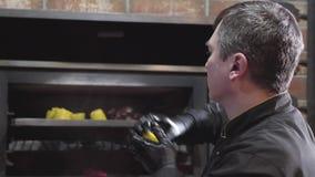 O cozinheiro chefe nas luvas pretas que põem na grade quente do forno cortou partes de grãos ao fritado lhes de todos os lados Fi filme