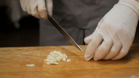 O cozinheiro chefe no alho dos cortes do restaurante em uma placa de madeira video estoque