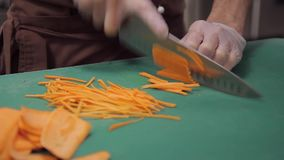 O cozinheiro chefe no uniforme corta cenouras finamente julienned da faca na tabela filme