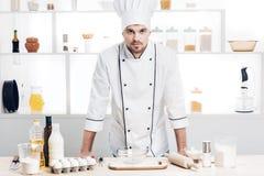 O cozinheiro chefe no uniforme está pronto para fazer uma massa na cozinha Fotografia de Stock