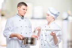 o cozinheiro chefe olha um prato cozinhado de um cozinheiro novo com acusação foto de stock