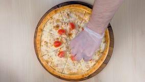 O cozinheiro chefe p?e tomates e alface sobre a pizza com galinha e o queijo na placa de madeira Entrega o close-up vídeos de arquivo
