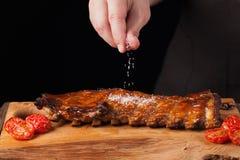 O cozinheiro chefe polvilha o sal nos reforços de carne de porco prontos para comer, encontrando-se em uma tabela de madeira velh imagens de stock
