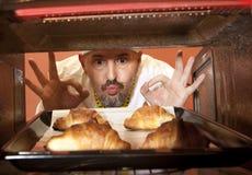 O cozinheiro chefe prepara o croissant no forno Imagem de Stock