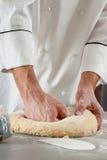 O cozinheiro chefe prepara a massa Foto de Stock