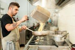 O cozinheiro chefe prepara a massa italiana em sua culinária foto de stock royalty free