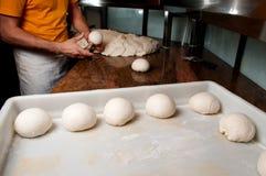 O cozinheiro chefe prepara a massa para a pizza Fotografia de Stock Royalty Free