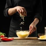 O cozinheiro chefe prepara o mozzarella, queijo Cheddar para a pizza italiana, massa Em um fundo preto, congelando-se no moviment fotos de stock