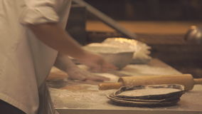 O cozinheiro chefe prepara a pizza Massa fina Desenrola a massa A cozinha no restaurante vídeos de arquivo