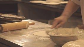 O cozinheiro chefe prepara a pizza Massa fina Desenrola a massa A cozinha no restaurante video estoque