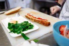 O cozinheiro chefe prepara um baguette com salmões em uma placa branca fotos de stock royalty free