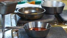 O cozinheiro chefe prepara um prato na cozinha do restaurante, cozinhando vegetais, abobrinha, molho do prigoshotovlenie, lado video estoque