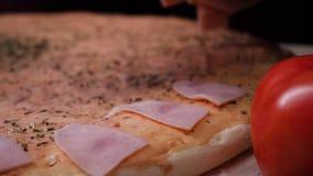 O cozinheiro chefe prepara uma pizza, pondo ingredientes sobre a massa Quadro Cozimento tradicional da pizza italiana imagens de stock royalty free