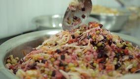 O cozinheiro chefe prepara uma salada fresca com vegetais em um grande prato filme