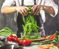 O cozinheiro chefe prepara vegetais para cozinhar na cozinha do restaurante imagem de stock royalty free