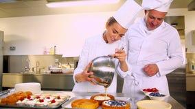 O cozinheiro chefe principal que olha seu estudante derrama o creme na caixa da pastelaria