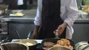 O cozinheiro chefe profissional cozinha costoletas com batatas trituradas em uma bandeja O cozinheiro trabalha em uma cozinha mod Fotos de Stock