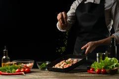 O cozinheiro chefe profissional polvilha camarões para a salada, o marisco e o conceito saudável do alimento Foto horizontal, men imagem de stock