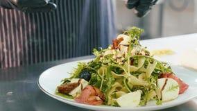 O cozinheiro chefe profissional polvilha com o caju uma salada fresca video estoque