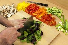 O cozinheiro chefe que desbasta alguma salada do babyleaf folheia com uma faca do talhador Imagem de Stock Royalty Free