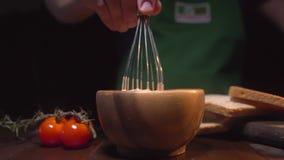 O cozinheiro chefe que os usos batem para misturar o molho na bacia, homem está cozinhando na cozinha, ingredientes para o molho, vídeos de arquivo