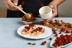 O cozinheiro chefe que o cozinheiro prepara o bruschetta italiano derrama o mel com morangos, queijo, camembert, brie, cozinhando fotografia de stock