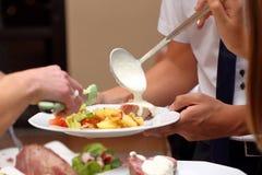 O cozinheiro chefe serve parcelas de alimento em um partido fotos de stock royalty free