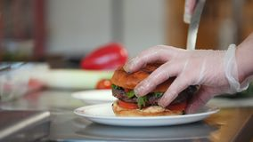 O cozinheiro chefe serve um hamburguer adicionando microplaquetas de batata em uma placa filme