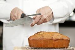 O cozinheiro chefe Sharpens a faca sobre o pão de banana Imagens de Stock