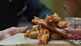 O cozinheiro chefe toma as lagostas vermelhas em uma grande bandeja de madeira Tentáculos deliciosos do caranguejo vermelho video estoque