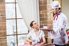O cozinheiro chefe traz a um prato a mulher bonita em um restaurante Fotografia de Stock