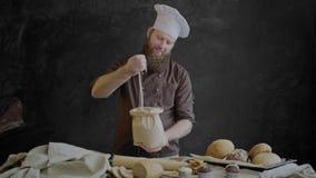 O cozinheiro chefe verifica a qualidade da farinha, estando perto de uma tabela decorada com as pastelarias de sua padaria filme
