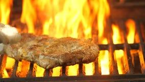 O cozinheiro chefe vira o bife grelhado diversas vezes com tenazes de brasa e olha quanto foi fritado, o vídeo é close-up video estoque