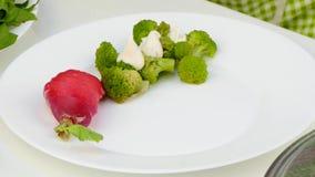 O cozinheiro coloca a galinha com vegetais em uma placa filme