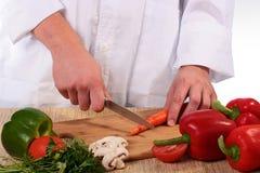 O cozinheiro corta cenouras Fotografia de Stock Royalty Free