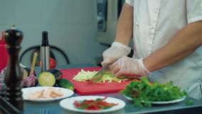 O cozinheiro corta a couve para a salada video estoque
