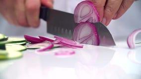 O cozinheiro corta lentamente a metade da cebola roxa filme