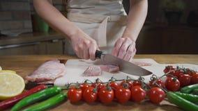 O cozinheiro corta peixes crus antes de cozinhar a refeição do marisco, os tomates com pimenta e os peixes crus, cozinhando peixe video estoque