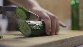 O cozinheiro corta um pepino em um fim da placa de madeira acima video estoque