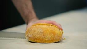 O cozinheiro cortou o pão quente na tabela vídeos de arquivo